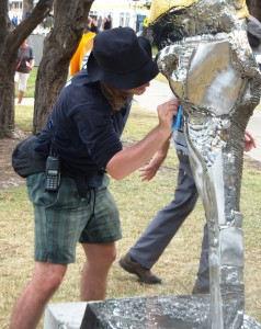 A workman scrubs rust from one of the exhibits